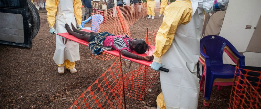 PHOTO: Two medical staff are bringing a weak patient who has been in contact with people infected with Ebola to the admission at MSF Ebola Treatment Centre in Kailahun, Sierra Leone.
