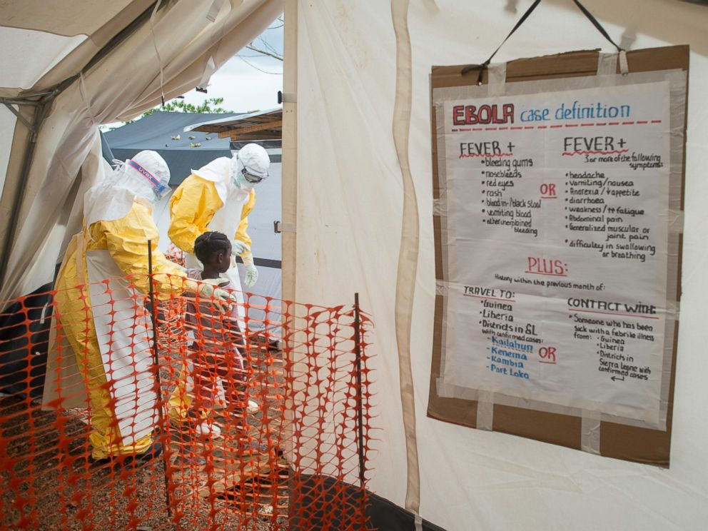 PHOTO: MSF staff show the way inside the Treatment Centre to a patient most likely infected with the Ebola virus/