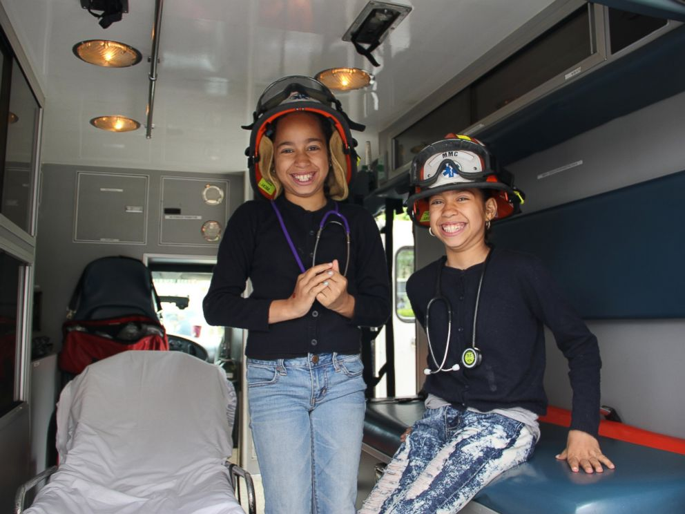 PHOTO: Ten-year-old twins Jayleen and Jayda check out an ambulance and try on EMT gear.