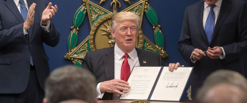 PHOTO: President Donald Trump holds up an executive order he signed at the Pentagon, where James Mattis, right, was also sworn in as defense secretary, in Arlington, Virginia, Jan. 27, 2017.