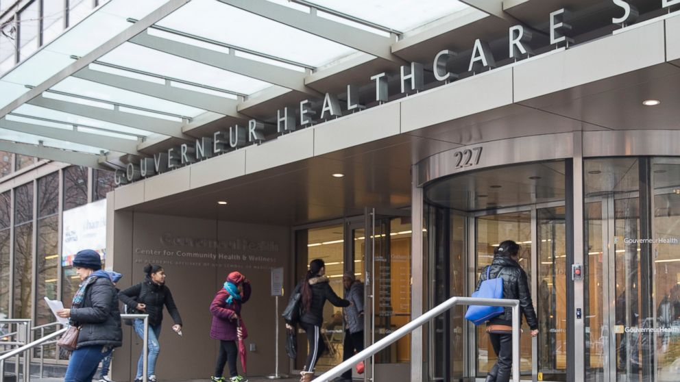 People enter New York City Health Hospitals Gouverneur Health building, Tuesday, Jan. 8, 2019, in New York. Mayor Bill de Blasio says New York City will spend up to $100 million per year to expand health care coverage to people without health insurance including immigrants in the U.S. illegally. (AP Photo/Mary Altaffer)