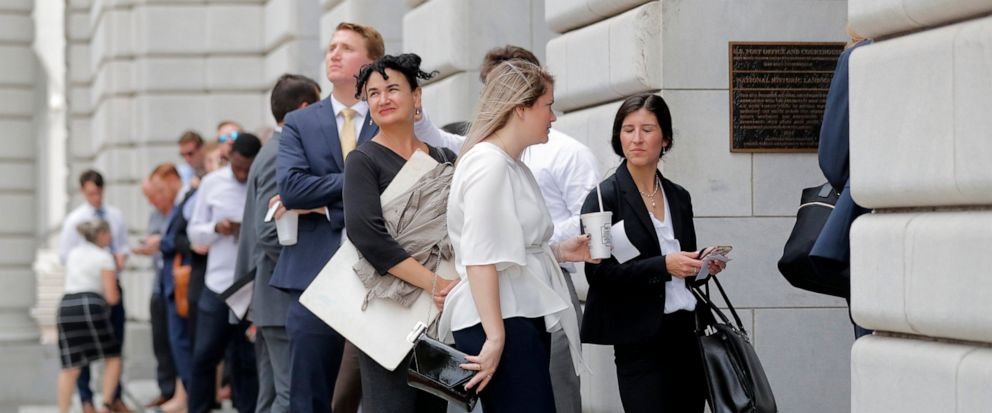 People wait in line to enter the 5th Circuit Court of Appeals to sit in overflow rooms to hear arguments in New Orleans, Tuesday, July 9, 2019. The appeals court will hear arguments today on whether Congress effectively invalidated former President B