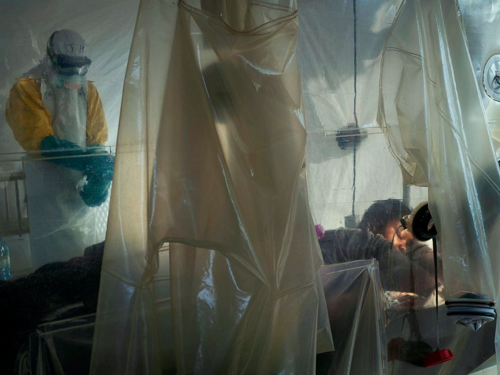 PHOTO: FILE - In this July 13, 2019 file photo, health workers wearing protective gear check on a patient isolated in a plastic cube at an Ebola treatment center in Beni, Congo.