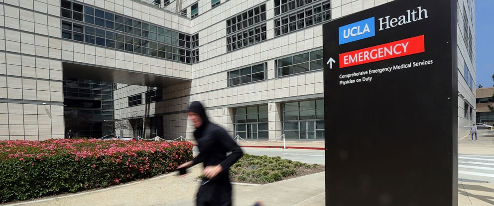 FILE - In this April 26, 2019, file photo, a runner passes the Ronald Reagan UCLA Medical Center on the campus of the University of California, Los Angeles. A woman says she was sexually assaulted by a gynecologist who worked for the University of Ca