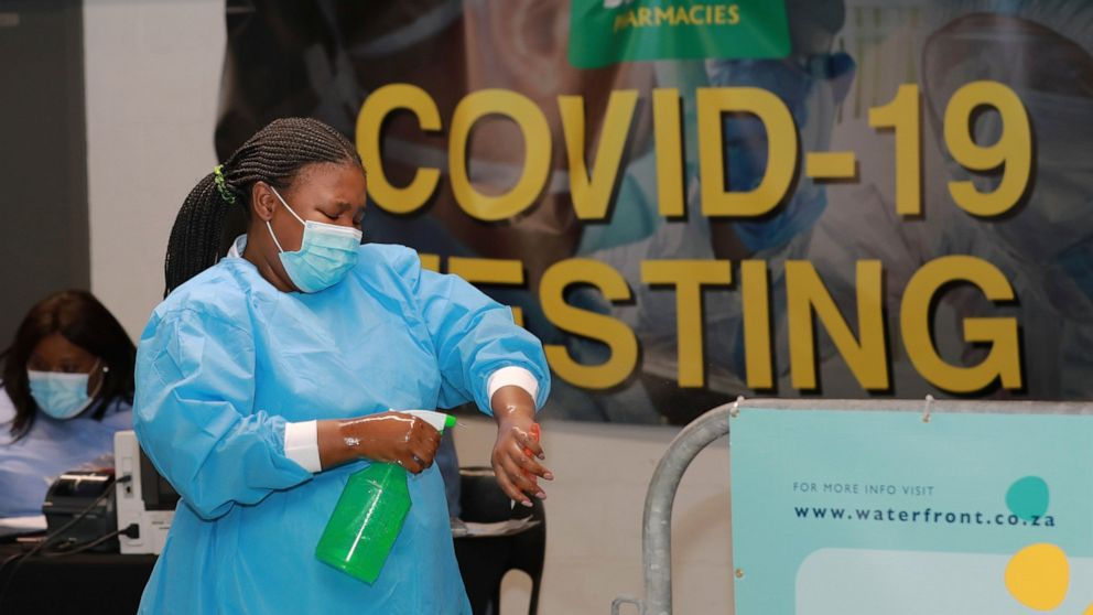 A health-care worker sanitises her hands before conducting COVID-19 tests at a Dis-Chem drive-through testing station at the V&A Waterfront in Cape Town, South Africa, Friday, Jan. 8, 2021. South Africa with 60 million people has reported by far the