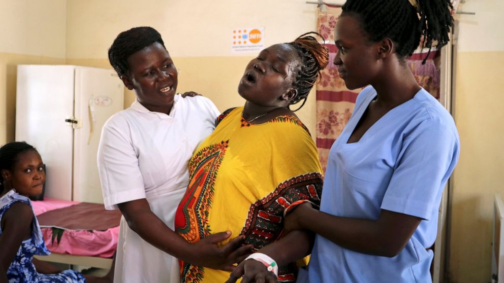 In this photo taken Monday, March 11, 2019, Aber Evaline, left, and another midwife, right, hold up a woman in labor and help her walk through the halls of the Juba Teaching Hospital, in the capital Juba, South Sudan. The country has one of the highest maternal mortality rates in the world but recently, despite a civil war that killed almost 400,000 people, maternal health has shown improvement after a concerted effort by the government and partners to dramatically increase the number of trained midwives. (AP Photo/Sam Mednick)