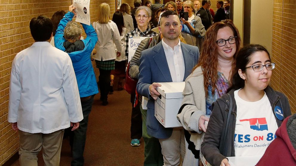 FILE - In this Oct. 24, 2019 file photo, supporters of Yes on 802 Oklahomans Decide Healthcare, calling for Medicaid expansion to be put on the ballot, carry boxes of petitions into the office of the Oklahoma Secretary of State, in Oklahoma City. Ten
