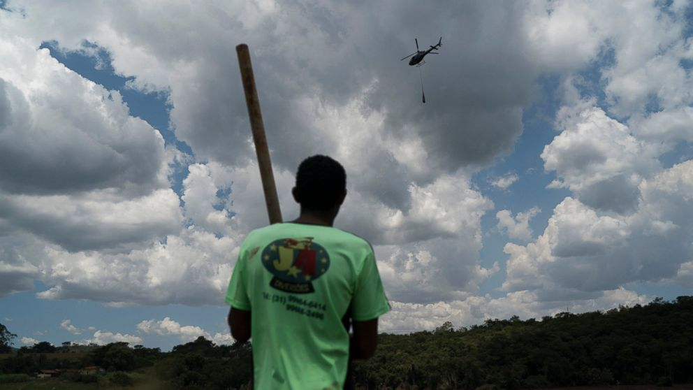 Fernando Nunes watches a helicopter carry a body away from the mud after a Vale dam collapse in Brumadinho, Brazil, Wednesday, Jan. 30, 2019, while his brother Peterson, a Vale employee, remains missing. Two days after this photo was taken, his brother's body was found, recovered and identified by their mother. (AP Photo/Leo Correa)