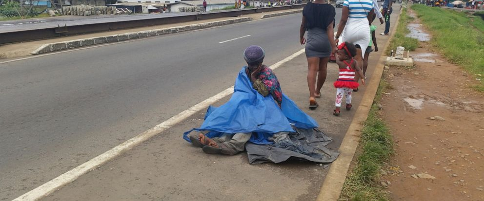 In this Oct. 9, 2019, photo, a mentally ill woman sits on the streets in Monrovia, Liberia. More than a decade after back-to-back civil wars ravaged Liberia its people still await justice for countless abuses, and many Liberians say the lack of accou
