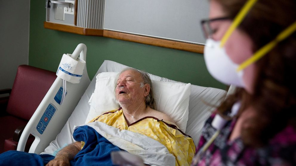 FILE - In this Friday, Feb. 9, 2018 file photo, Henry Beverly, 73, battles the flu while tended to by nurse Kathleen Burks at Upson Regional Medical Center in Thomaston, Ga. As of January 2019, the current flu season is shaping up to be gentler than last winter's unusually brutal one, health officials say. (AP Photo/David Goldman)