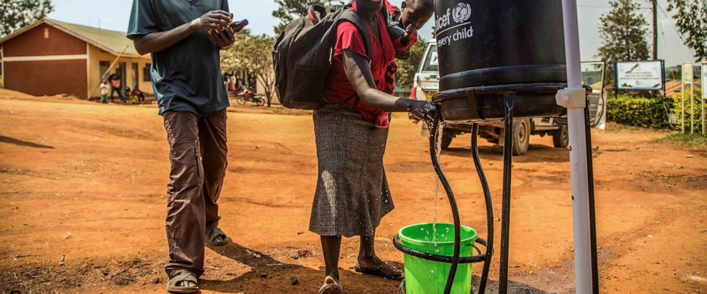 In this photo provided by the International Rescue Committee, Congolese refugees wash their hands before being screened for Ebola symptoms at the IRC triage facility in the Kyaka II refugee settlement in Kyegegwa District in western Uganda, Thursday,