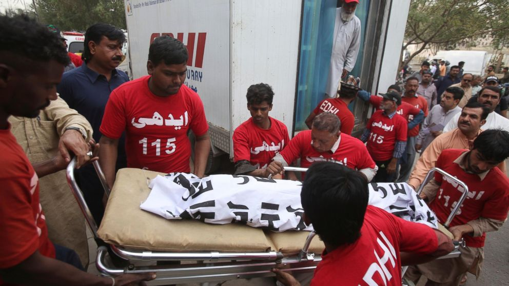 Pakistani volunteers move the body of a food poisoning victim to a mortuary in Karachi, Pakistan, Friday, Feb. 22, 2019. Pakistani police say many children have died of suspected food poisoning after their family had dinner at a restaurant in the country's south. (AP Photo/Fareed Khan)
