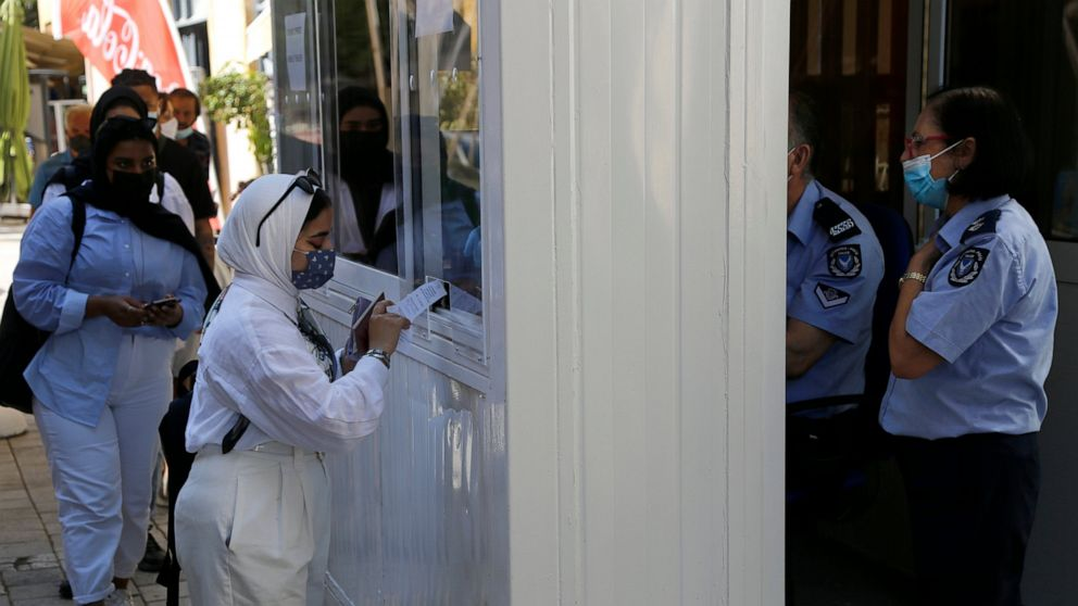 A woman wearing protective face mask, shows her COVID-19 test to a police officer at Ledra crossing point in divided capital Nicosia, Cyprus, Friday, June 4, 2021. Ethnically split Cyprus took a key step toward a return to its normal rhythms of life
