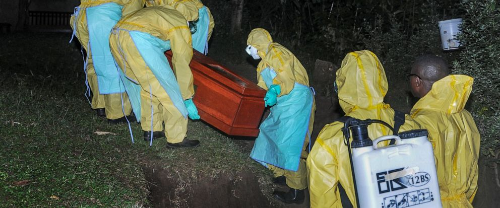 Workers wearing protective clothing bury Agnes Mbambu who died of Ebola, the 50-year-old grandmother of the 5-year-old boy who became Ebolas first cross-border victim, in the village of Karambi, near the border with Congo, in western Uganda Thursday