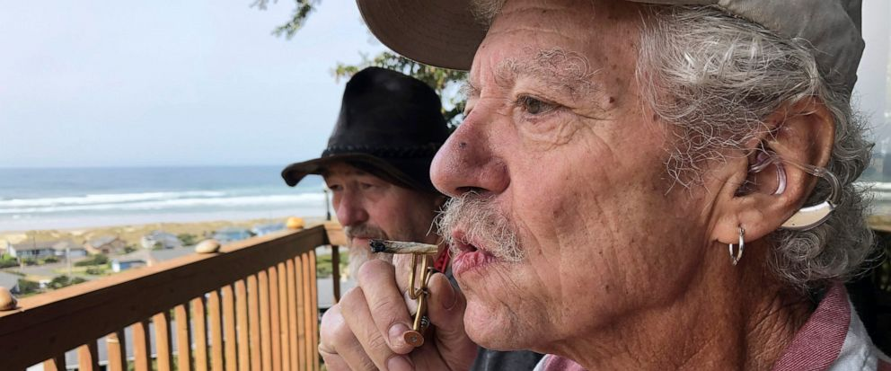 ADVANCE FOR PUBLICATION ON TUESDAY, JUNE 11, AND THEREAFTER - In this April 25, 2019, photo, two-time cancer survivor and medical marijuana cardholder Bill Blazina, 73, smokes a marijuana joint on the deck of his neighbors home in Waldport, Ore. Bla