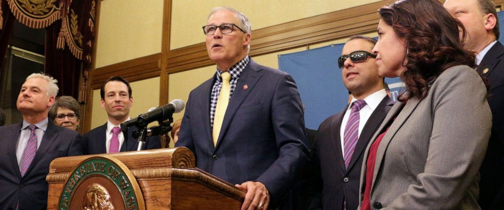 FILE - In this April 29, 2019, file photo, Gov. Jay Inslee, surrounded by Democratic lawmakers from the Senate and House, talks to the media following the Washington Legislature adjourning its 105-day legislative session in Olympia, Wash. Inslee is e