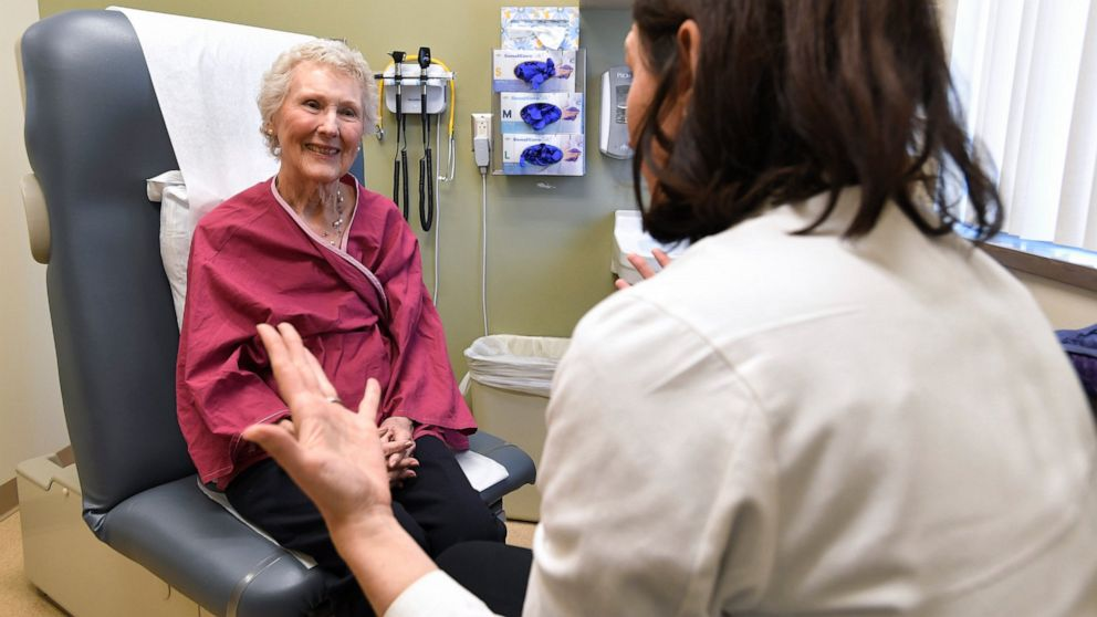 """In this Monday, March 4, 2019, Nancy Simpson, left, speaks with Dr. Allison Magnuson, Geriatric Oncology and Breast Oncology at Wilmot Cancer Institute, at the Pluta Cancer Center in Rochester, N.Y. Simpson, 80, says she """"wanted to do the maximum I could handle"""" to fight her disease. (AP Photo/Adrian Kraus)"""