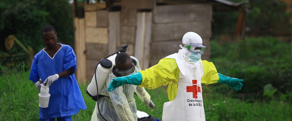 FILE - In this Sunday, Sept 9, 2018 file photo, a health worker sprays disinfectant on his colleague after working at an Ebola treatment centre in Beni, Eastern Congo. Congos health ministry says a baby has been born to a mother who recovered from t