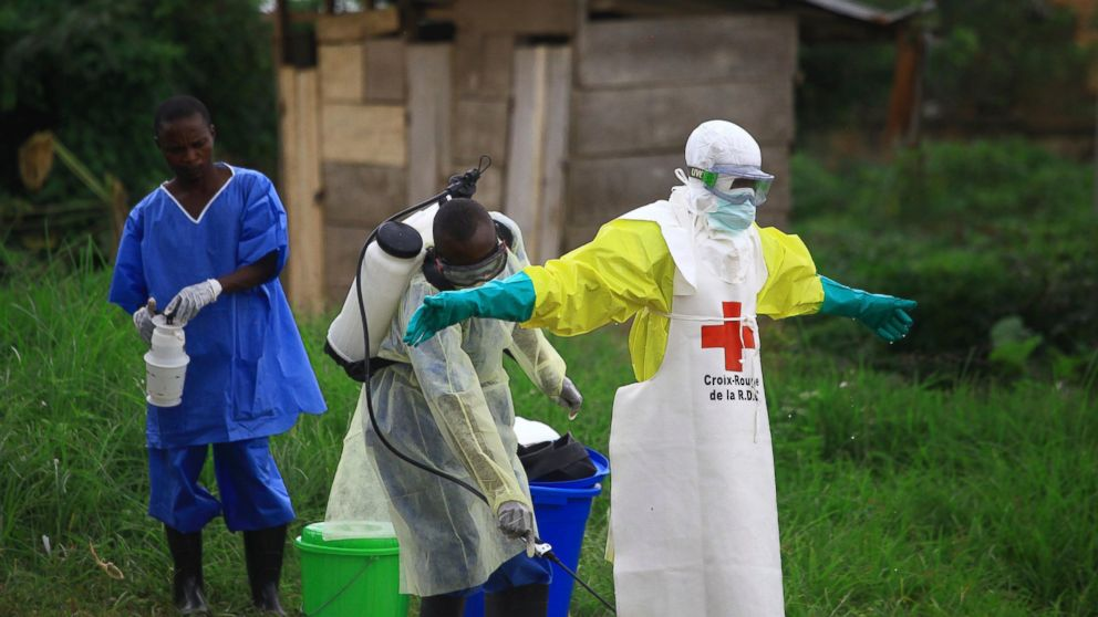 """FILE - In this Sunday, Sept 9, 2018 file photo, a health worker sprays disinfectant on his colleague after working at an Ebola treatment centre in Beni, Eastern Congo. Congo's health ministry says a baby has been born to a mother who recovered from the Ebola virus _ a bright spot in an outbreak that is the second-deadliest in history. The health ministry tweeted a photo of """"baby Sylvana"""" in her smiling mother's arms. The baby does not have the virus. The ministry says Sylvana is the first baby in this outbreak born to a mother who has recovered. (AP Photo/Al-hadji Kudra Maliro, file)"""