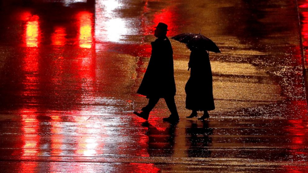 FILE - In this Dec. 26, 2018 file photo, pedestrians are silhouetted against wet pavement as they walk in the Country Club Plaza shopping district in Kansas City, Mo. The number of pedestrians killed on U.S. roads last year was the highest in 28 years, according to a report from a safety organization. Using data reported by states, the Governors Highway Safety Association estimates that 6,227 pedestrians were killed last year. That's up 4 percent from 2017 and 35 percent since 2008. (AP Photo/Charlie Riedel, File)