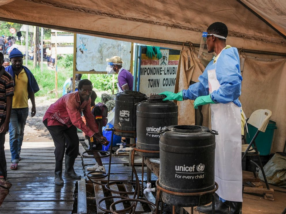 FILE - In this Friday, June 14, 2019 file photo, people coming from Congo wash their hands with chlorinated water to prevent the spread of Ebola infection, at the Mpondwe border crossing with Congo. Ugandan health authorities on Thursday, Aug. 29, 20