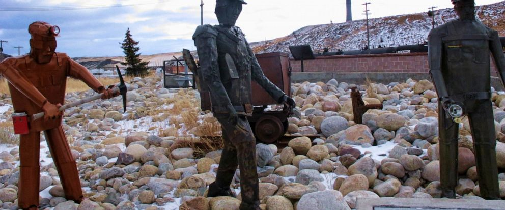 FILE - This Dec. 13, 2016, file photo, shows the former Anaconda smelter smokestack behind sculptures of miners at the Anaconda Smelter Stack State Park viewing area in Anaconda, Montana. Residents in the nearby community of Opportunity are suing to