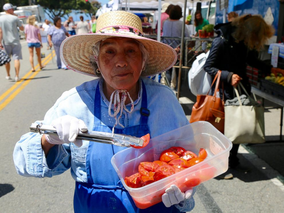 PHOTO: A woman offers samples of tomatoes at the Santa Monica Farmers Market in Los Angeles, June 14, 2017.