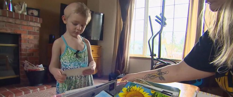 PHOTO: Elie Walton, a 3-year-old with terminal brain cancer, plays with postcards sent to her from all over the world.