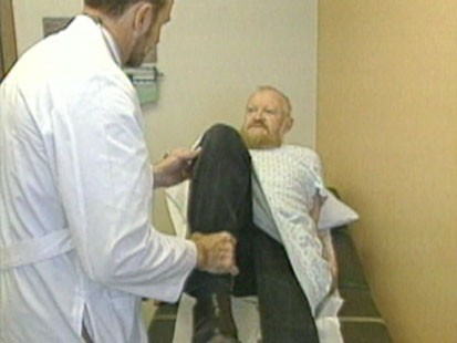 A picture of a docter bending someones knee.
