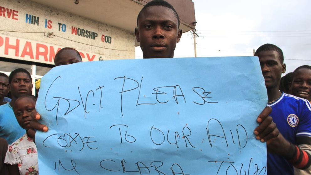 A young man holds a sign at a protest about the delayed removal of a suspected Ebola victim who had died in Clara Town, Liberia, on Thursday. On Saturday morning, community members learned that the dead man's neighbor had also died.