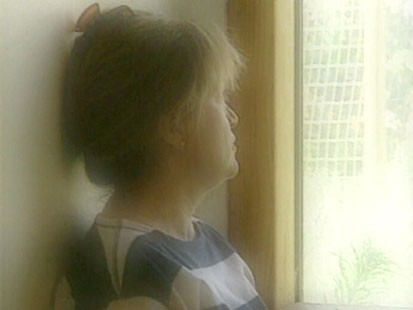 A picture of a woman looking out the window.