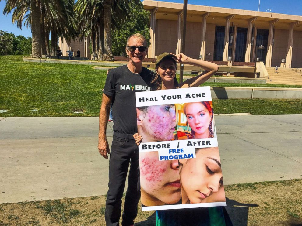 PHOTO: Nina Nelson and her father, Jeff Nelson, pose with a sign recruiting college students.