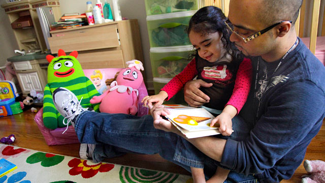 PHOTO: Christopher Astacio reads with his daughter Cristina, 2, recently diagnosed with a mild form of autism, in her bedroom, March 28, 2012 in New York.