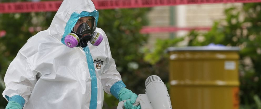 PHOTO: A hazmat worker clean outside the apartment building of a hospital worker, Sunday, Oct. 12, 2014, in Dallas.