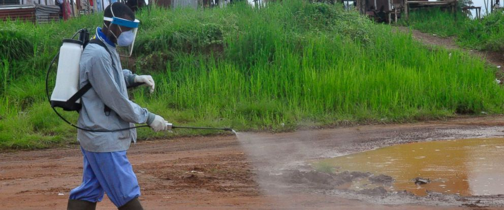 PHOTO: Ebola health workers spray disinfectant on a road near the home of a 17-year old boy that died from the Ebola virus on the outskirts of Monrovia, Liberia, July 1, 2015.
