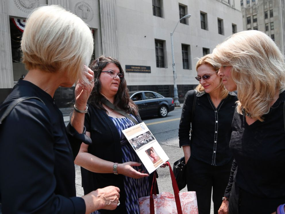 PHOTO: Liz Lupo, second from left, shows a sign in honor of her mother, Marianne Lupo, a former patient of Dr. Farid Fata, outside federal court, Monday, July 6, 2015, in Detroit.