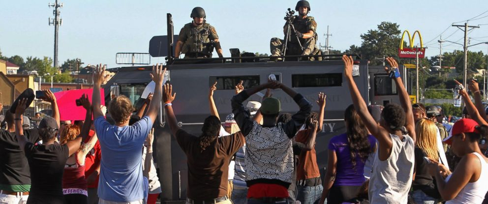 PHOTO: Protesters raise their hands in front of police atop an armored vehicle in Ferguson, Mo. on Aug. 13, 2014.