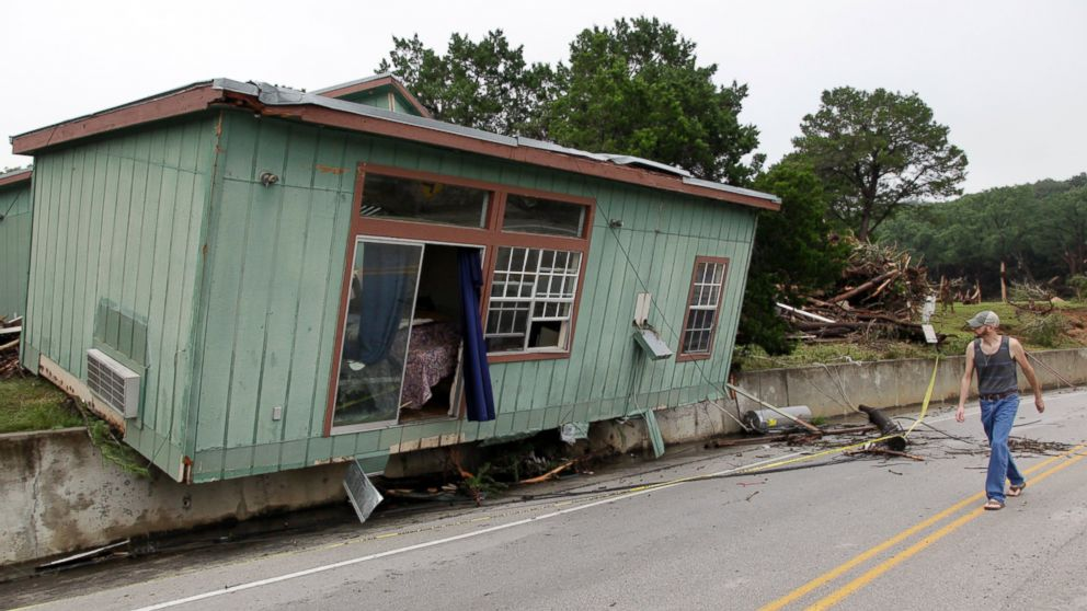 A man walks past a cabin that was torn from its foundation in a flood on the Blanco River days earlier, May 26, 2015, in Wimberley, Texas.