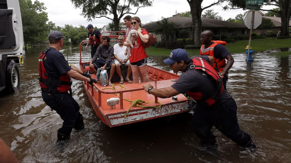 Members of the Houston Fire department help residents evacuate through the floodwaters surrounding their homes in Houston, May 26, 2015.