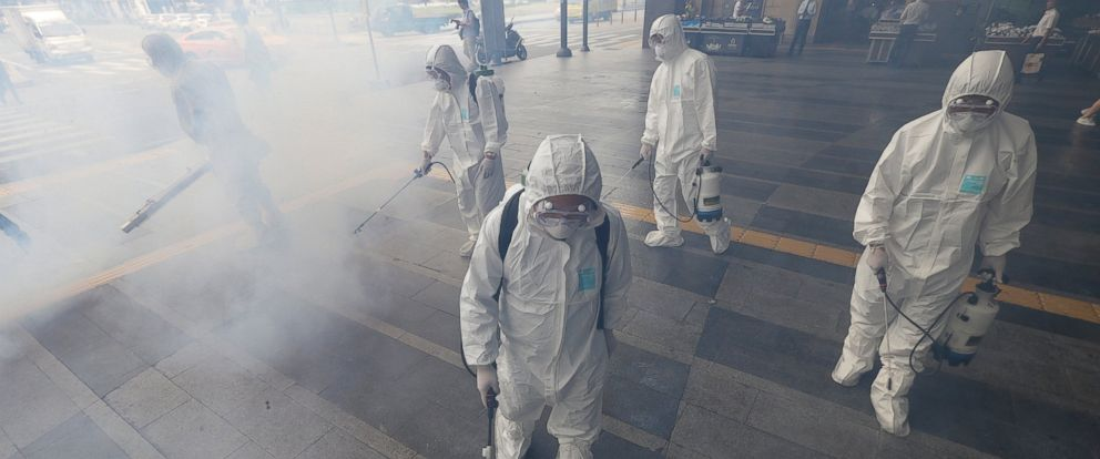 PHOTO: Workers wearing protective gears spray antiseptic solution as a precaution against the spread of MER virus outside Wangsimni Subway Station in Seoul, South Korea, June 11, 2015.