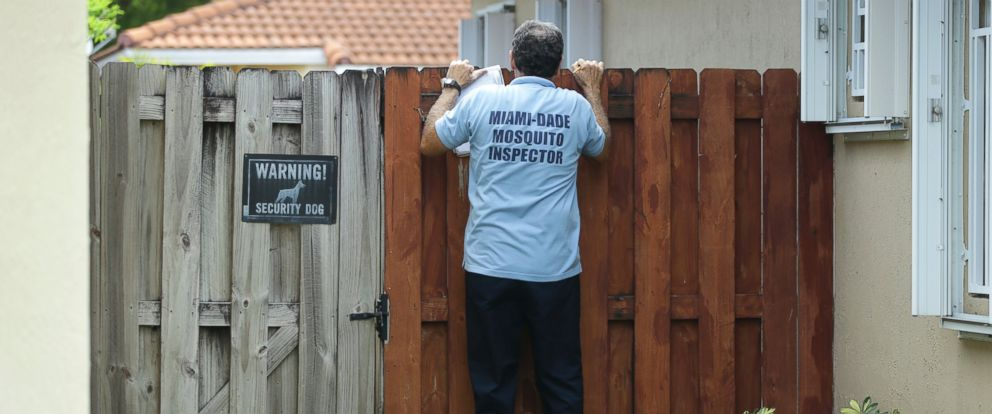 PHOTO: Giraldo Carratala, an inspector with the Miami Dade County mosquito control unit, peers over a fence into the back yard of a home, April 12, 2016, in Miami, Fla.