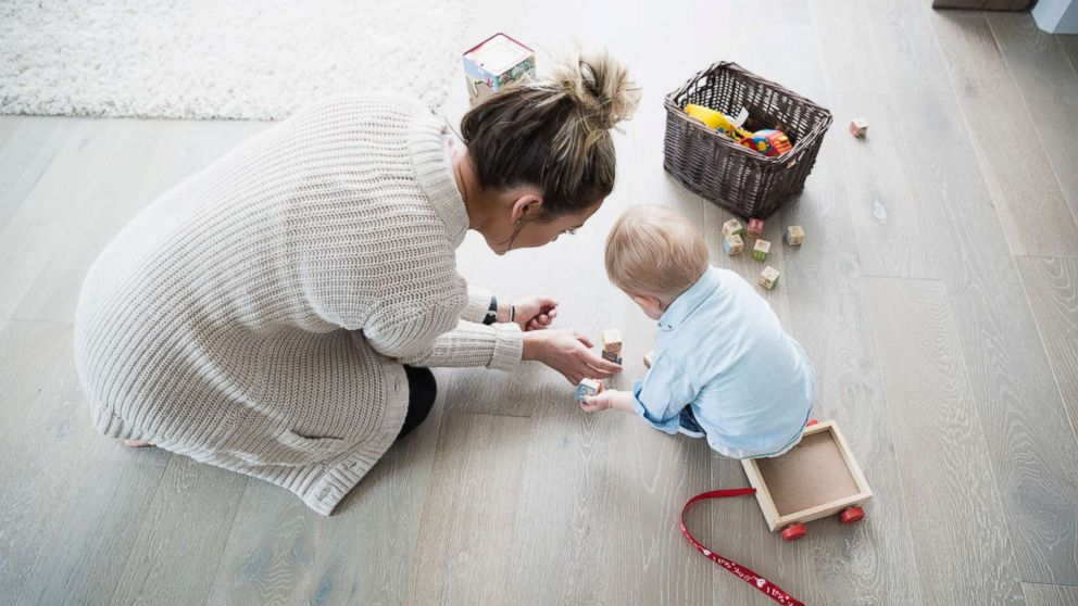 Mother and baby son playing with wood blocks in an undated stock photo.