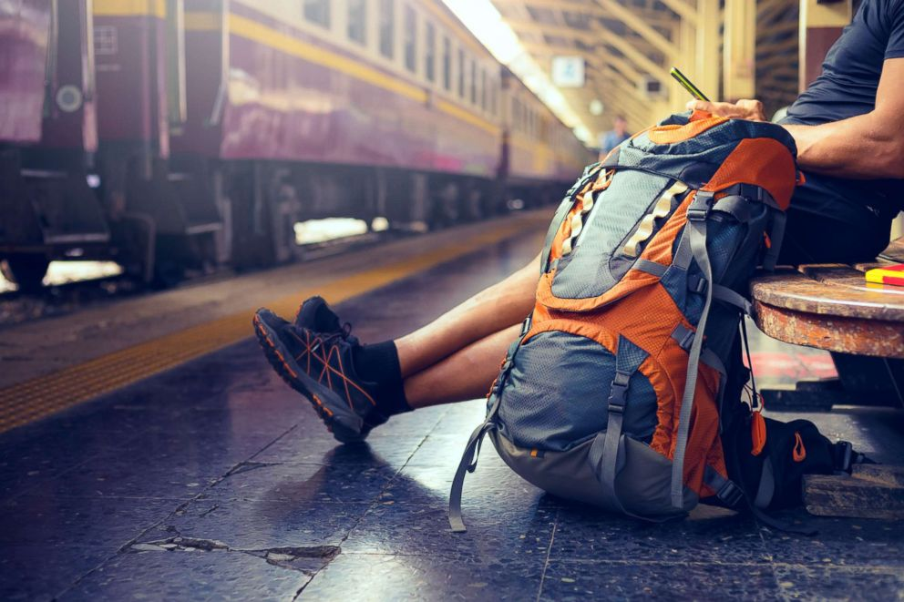 This stock image depicts a tourist with a backpack waiting for a train.