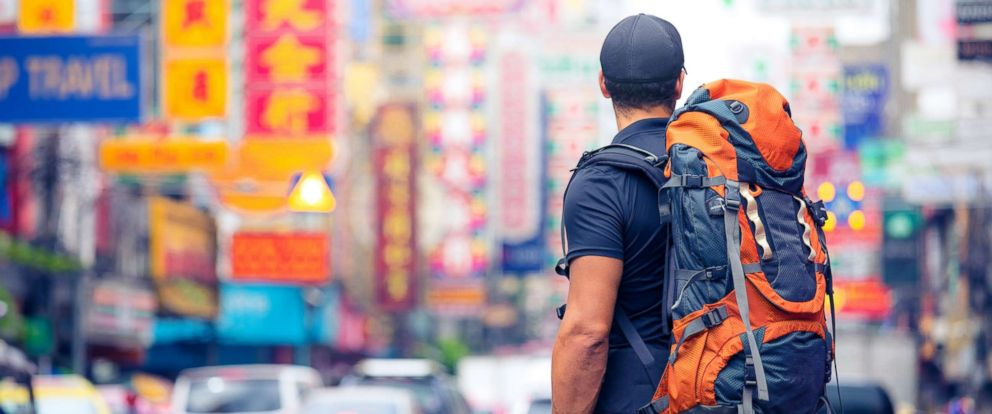 ea77321d1468 PHOTO  This stock image depicts a tourist wearing a backpack arriving in a  new city
