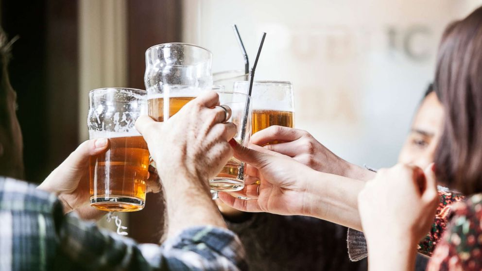 People toast with beer mugs at a pub in an undated stock photo.