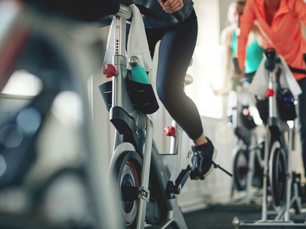 PHOTO: Women work out on exercise bikes at a gym.
