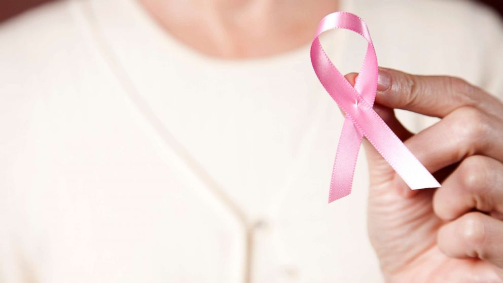 In this undated stock photo, a woman wearing a pink sweater holding a pink breast cancer ribbon.