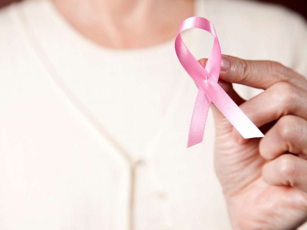 PHOTO: In this undated stock photo, a woman wearing a pink sweater holding a pink breast cancer ribbon.
