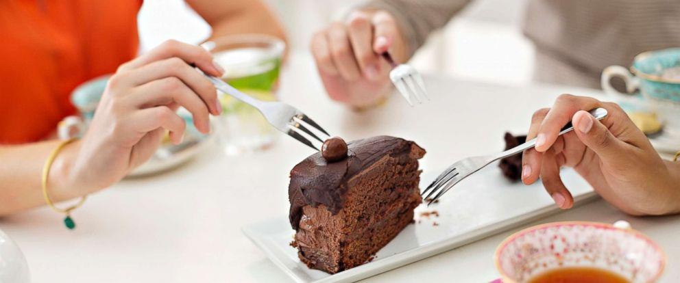 PHOTO: Women sharing aslice of cake.