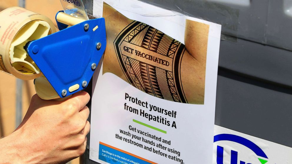 A worker tapes signage telling people to get vaccinated to protect themselves against hepatitis A on hand washing sinks installed at the Neil Good Day Center in downtown San Diego, Sept. 1, 2017.